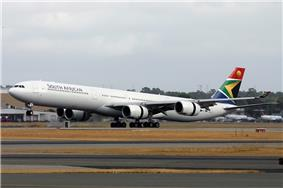 An Airbus A340-600 in the current livery. It is landing on a runway, facing left.