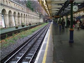 View along station platform with timber and glass canopy over supported on cast-iron columns. To the left a disused platform without track is visible