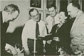 Four middle-aged men are gathered around to listen to a woman sing from a book