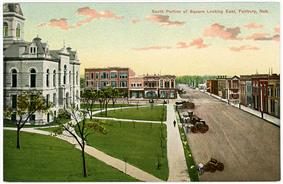 Old postcard, showing courthouse and commercial streets; several horse-drawn vehicles on street