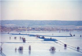 Photograph from elevation of flooded river flowing between snow-covered fields. Hills in the distance.