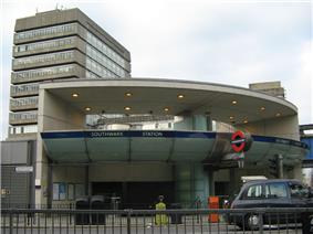 A grey building with a rectangular, dark blue sign reading