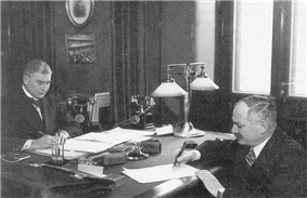 Two men sign papers at opposite sides of a table in a small office.