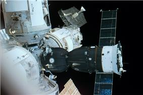 An image of the four radial modules of the space station, with a Soyuz spacecraft, seen docked to the centre of the cluster. The Soyuz consists of a spherical orbital module, headlight-shaped descent module and cylindrical service module to which are attached two blue solar arrays. The entire spacecraft is covered in dark insulation except the base of the service module, which is white.