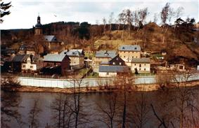View of a small village with houses and a church, located in a wooded valley, with a river in the foreground. A high concrete wall separates the village from the river.