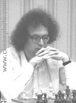 black and white photograph of dark-haired male wearing glasses, seated at chess game
