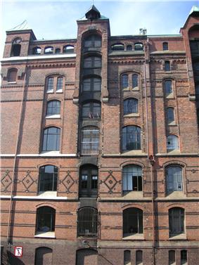 A red brick multi-storey house in Neo-Gothic style with little towers and other ornamental features.