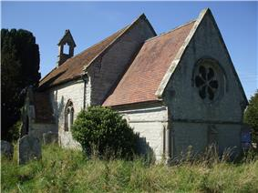 A stone church seen from the south east with steep tiled roofs. Nearest is the chancel with a round east window, beyond that is a larger, higher nave, at the end of which is a bellcote
