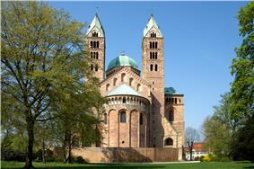 Looking toward the choir of a brick Romanesque cathedral. The twin bell towers, the transept crossing dome, and the roof are green copper.