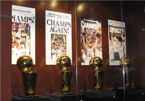 Four trophies on display behind a glassed wall