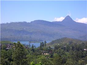 Forested mountains, a settlement, a lake and a characteristic peak in the distance.