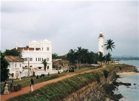 A white church and white lighthouse near the sea.
