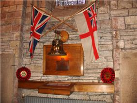 The White Ensign and Union Flag are crossed together on an interior stone wall above a brass bell and wooden plaque. Beneath this is a glass and wood cabinet. Poppy wreaths lie to either side.