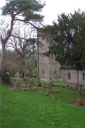 A stone church in a graveyard behind evergreen trees