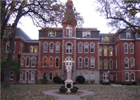 A statue sits in front of a large four-story red brick building. To the right of the entrance, the building goes in a little ways, and then back out. To the left of the entrance is a small two-story area connecting the main part of the building to the rest of it. Above and behind the two-story part is a four-story part of the building