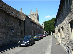 Street of grey stone houses. The church tower can be seen n the background