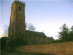 Stone building with square tower, partially obscured by trees.