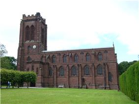 A stone Gothic Revival church with a battlemented tower