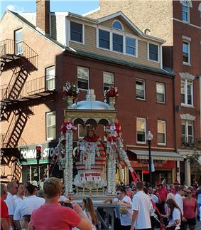 A life size statue of St. Agrippina di Mineo in a ornate canopy accompanied by the North End Marching Band.