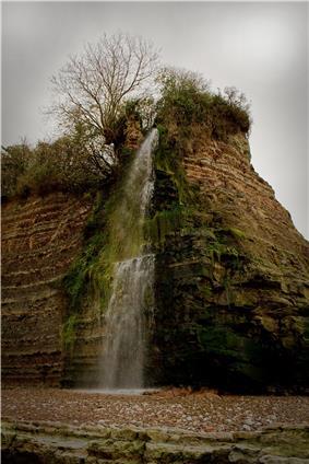 Waterfall cascading down rockface.