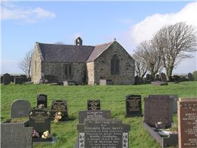 At the far end of a graveyard is a simple stone church, which appears L-shaped, and has a bellcote