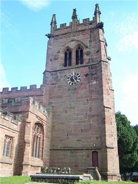 A stone Gothic tower with a clock face