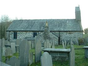 The north side of stone church with a slate roof, seen through a graveyard. There are two windows, a protruding vestry and, at the right, a bellcote