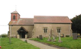 Side view of a building, which has a small tower on the left side: tombstones lie in rows on plots in front.