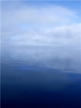 A calm, flat river surface with clouds and fog obscuring the horizon line