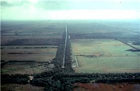 Aerial view of agricultural fields through the middle of which is a drainage canal