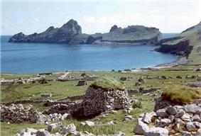 A rocky bay with stone ruins in the foreground. The ocean enters the picture from the left and across the bay several rocky crags are visible sticking out the sea.