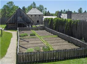View of a vegetable garden, buildings and stockades at the reconstructed Sainte-Marie Among the Hurons Mission