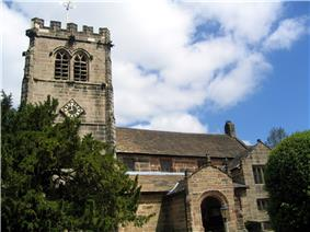 A stone church with a battlemented Gothic tower