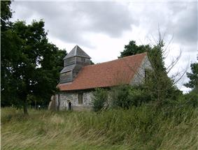 A flint church seen from the southeast, with a red tiled roof and, at the far end, a weatherboarded tower