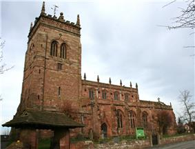 A Gothic stone church with a tower on the left