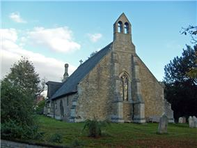 The west end of a stone church seen from a slight angle, showing two large buttresses with a window between, a double bellcote above, and part of the body of the church with its thatched roof