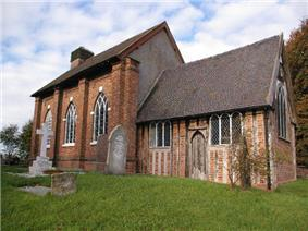 A church with a brick nave on the left, and a smaller timber-framed chancel on the right