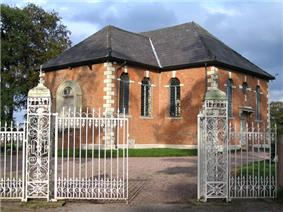 A small Neoclassical brick chapel with a slate roof