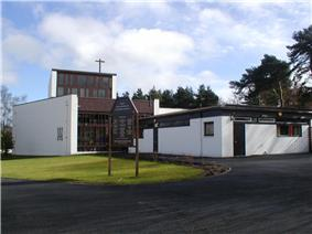 Modernist Church coated with white render with large modern stained glass window and a wooden cross protruding from the roof of the two storey tower element of the building