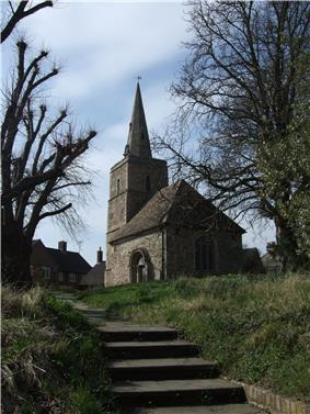 A flight of steps leads up to a stone church with a tower and steeple
