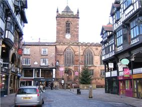 A stone Gothic church with a tower surmounted by a pyramidal roof see at the end of a street