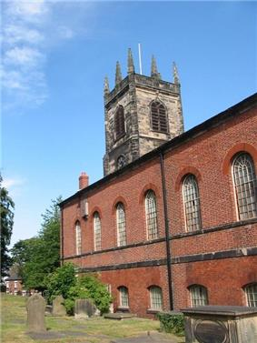 The brick Neoclassical body of a church with a stone Gothic tower behind