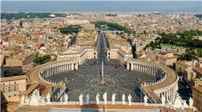 At the front of the view are the backs of thirteen large statues that stand in along the edge of the façade. Beyond them can be seen the piazza which is in three parts. The nearest appears square, while the second widens into an oval surrounded on each side by the huge grey columns on the colonnade, and with the obelisk at its centre. Beyond that is a further square surrounded by pale pink buildings. A wide street leads from the square, at the end of which can be seen the river, a bridge and castle.