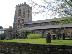 A stone Gothic church with a battlemented tower on the left