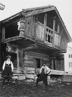 Crude log and timber open-air cabin with a pitched roof on a foundation of rocks, with the second storey overhanging the first.