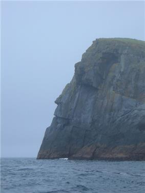A tall grey rocky cliff towers over dark waters. The edge of the cliff is silhouetted against a leaden sky and topped with grass, creating a shape resembling a man's face.