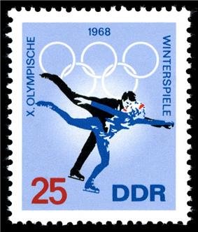A postage stamp with a blue background and two figure skaters skating, the date 1968 is centered on the top of the stamp along with the Olympic rings. The word