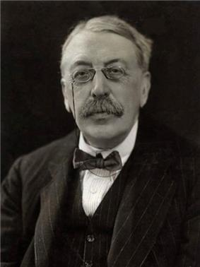 head and shoulders shot of an elderly man with full head of hair, moustache and pince-nez