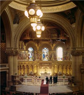 12 An interior view looking from high in the gallery, past two large arches which support the dome, and into the lofty semi-circular chancel. The building is of very large scale, and every part of the interior is covered with mosaic or carved decoration. In the chancel, a priest officiates for a bride and groom with eleven attendants.