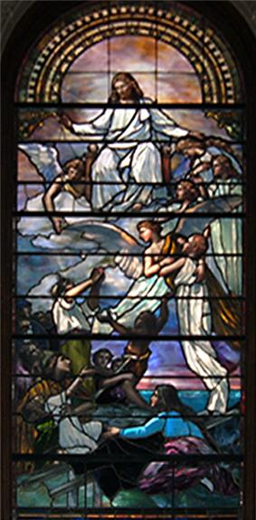 This stained-glass window shows two angels carrying a small child up towards Christ seated on golden clouds in while a group of people below are watching.